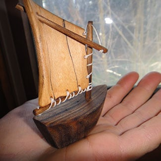 tiny sailboat held in someone's palm