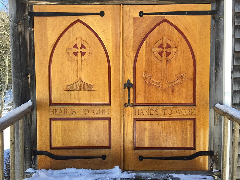 "carved wooden door with text ""hearts to god, hands to work"""