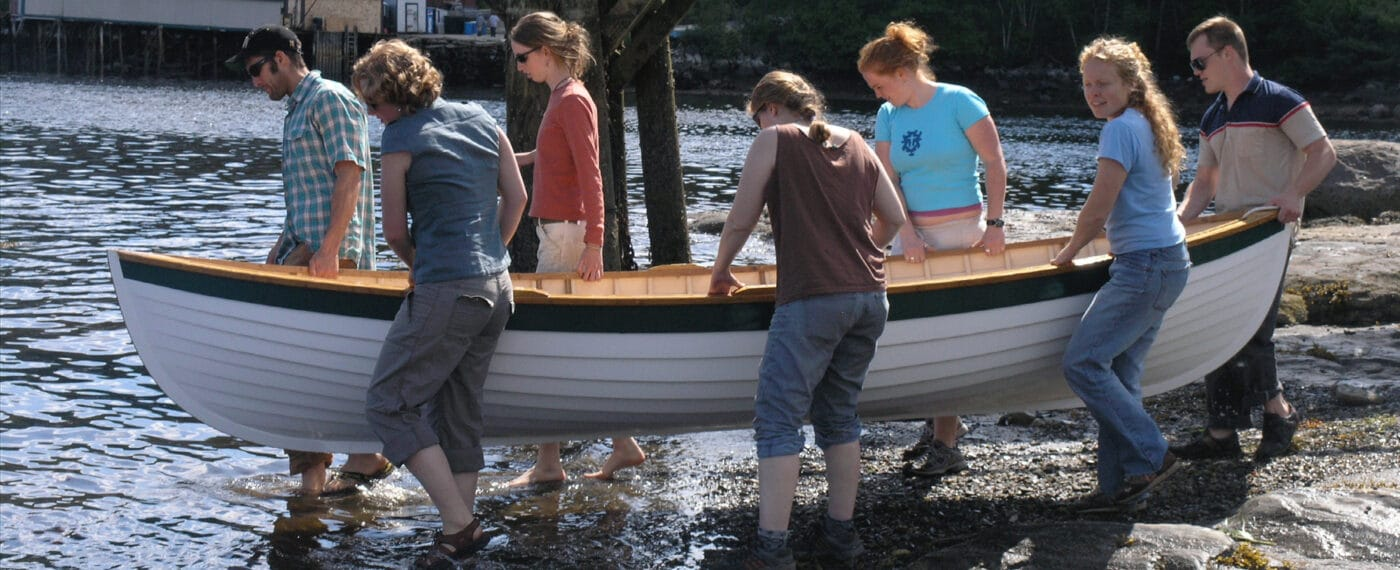 apprentices wading in to launch a dinghy
