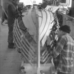 apprentices working on the hull of a skiff