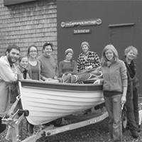 apprentices pose by a catspaw dinghy